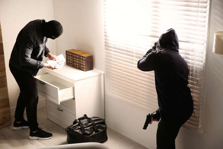 Dangerous masked criminals with weapon stealing money from house