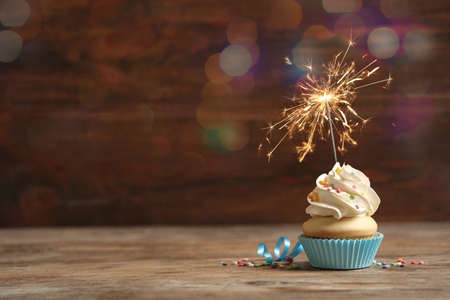 Birthday cupcake with sparkler on wooden table, space for text. Bokeh effect