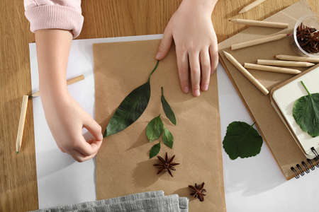 Little girl working with natural materials at table, top view. Creative hobby