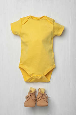 Child's bodysuit and booties on white wooden background, flat lay