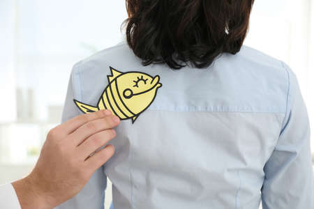 Man sticking paper fish to colleague's back in office, closeup. April fool's day