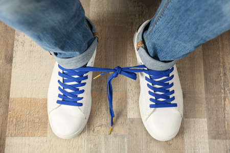 Man wearing sneakers with tied together laces, top view. April fool's day Stock Photo