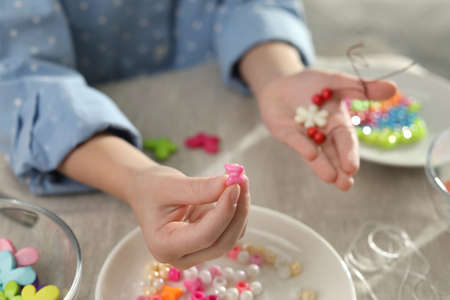 Little girl making accessory with beads at table, closeup. Creative hobby
