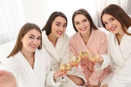 Belles jeunes femmes avec des verres de vin prenant selfie à la fête à l'intérieur. Le jour de la femme