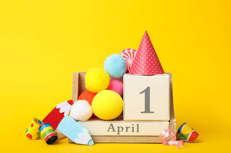 Wooden block calendar and party decor on yellow background. April fool's day