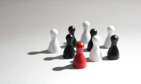Red game piece among black and white ones on light grey background. Career promotion concept 版權商用圖片
