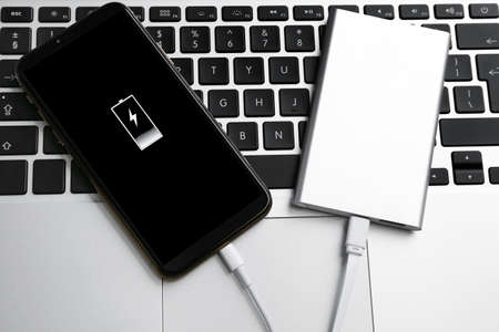 Modern smartphone charging with power bank on laptop, closeup