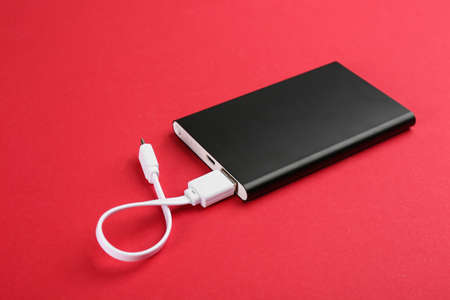 Modern portable charger with cable on red background