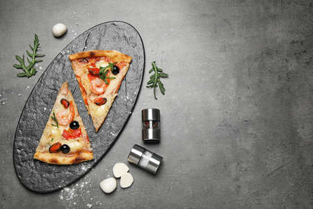 Tasty pizza with seafood and ingredients on grey table, flat lay. Space for text Banque d'images