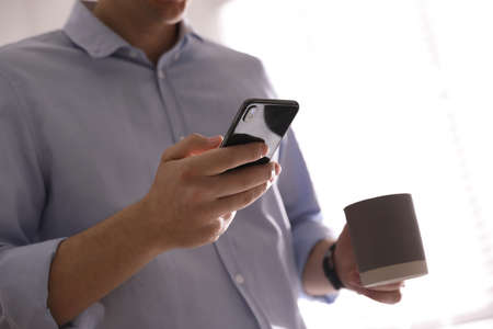 Man with cup and smartphone against light background, closeup of hands