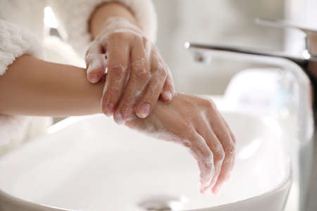 Woman washing hands with soap over sink in bathroom, closeup