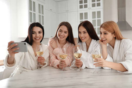 Beautiful young ladies with wine taking selfie in kitchen at pamper party. Womens Day