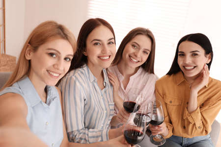 Beautiful young ladies with wine taking selfie indoors. Womens Day