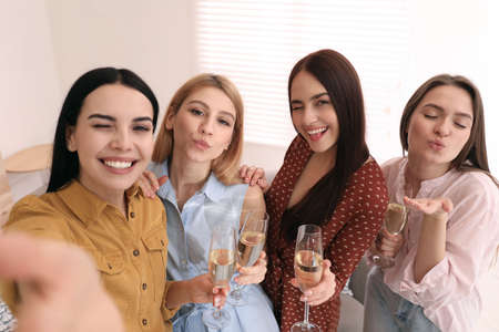 Beautiful young ladies with champagne taking selfie at home. Womens Day