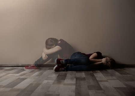 Upset little girl alone near beige wall. Autophobia