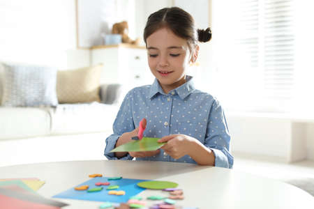 Little girl making greeting card at table indoors. Creative hobby