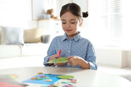 Petite fille faisant la carte de voeux à table à l'intérieur. Passe-temps créatif