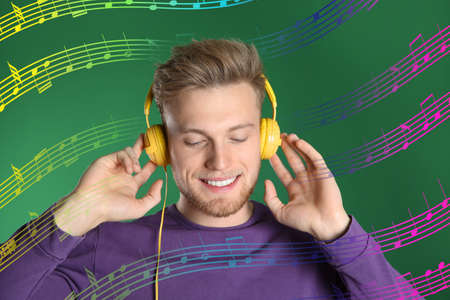 Handsome young man listening music with headphones on green background