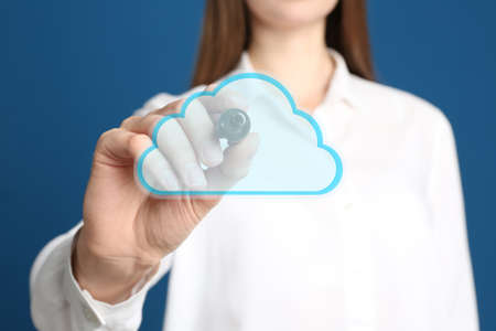 Woman pointing at virtual cloud icon on blue background, closeup of hand. Data storage concept Banque d'images
