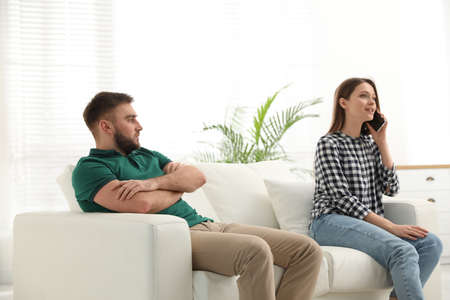 Young woman with smartphone ignoring her boyfriend at home. Relationship problems Stock Photo