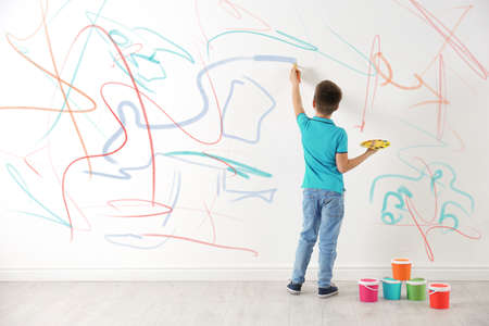 Little child drawing scribbles on white wall indoors
