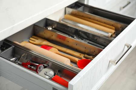 Different utensils in open desk drawer indoors, closeup