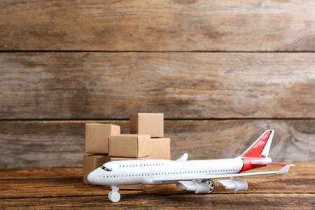Airplane model and carton boxes on wooden background, space for text. Courier service