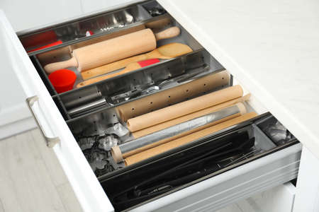 Different utensils in open desk drawer indoors