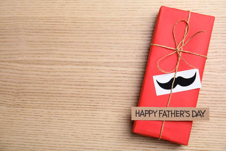 Gift box with mustache and words HAPPY FATHER'S DAY on wooden background, top view. Space for text Stok Fotoğraf