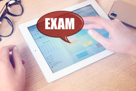 Student using tablet at wooden table, closeup. Online exam