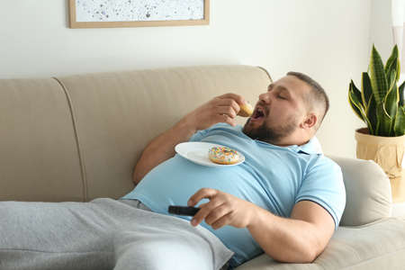 Lazy overweight man with donuts watching TV on sofa at home