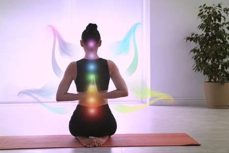 Young woman with chakra points practicing yoga in studio, back view. Healing energy