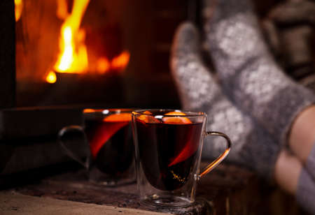 Tasty mulled wine in glass cups near fireplace indoors