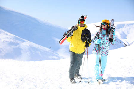 Young couple with skis on hill, space for text. Winter vacation