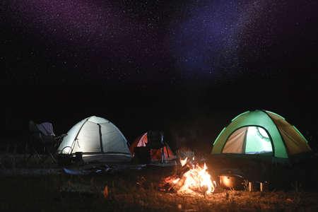 Lagerfeuer in der Nähe von Campingzelten im Freien nachts