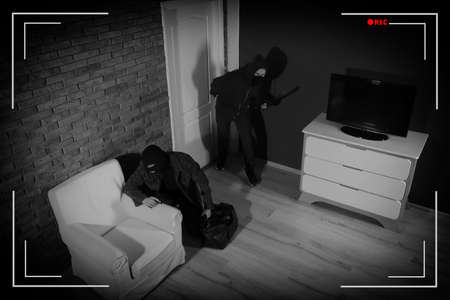 Dangerous criminals in masks with weapon robbing house, view through CCTV camera