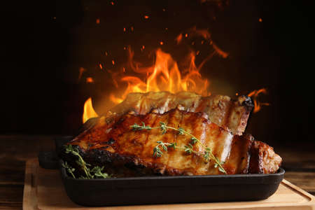 Tasty grilled ribs and flame on wooden board Foto de archivo