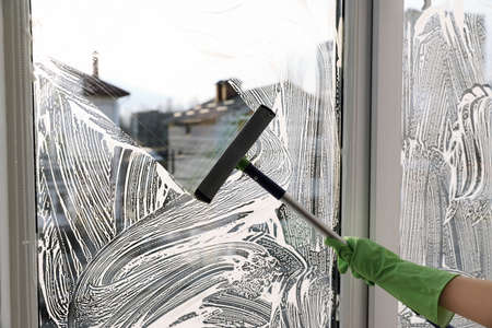 Woman cleaning window with squeegee indoors, closeup