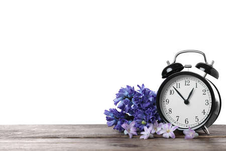 Black alarm clock and spring flowers on wooden table against white background, space for text. Time change