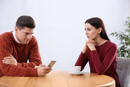 Man preferring smartphone over his girlfriend in cafe. Relationship problems