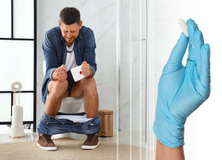 Doctor holding suppository for hemorrhoid treatment and man sitting on toilet bowl in rest room