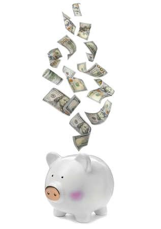 Dollars falling into piggy bank on white background Standard-Bild