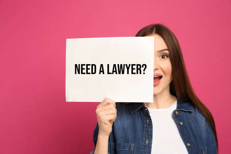 Emotional woman holding paper with text NEED A LAWYER? on pink background
