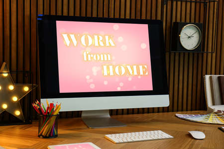 Modern computer with text WORK FROM HOME on table in office Stock Photo