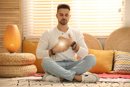 Young man during self-healing session in therapy room Archivio Fotografico