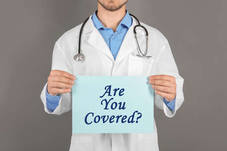 Doctor holding paper with text ARE YOU COVERED? on grey background, closeup. Insurance concept