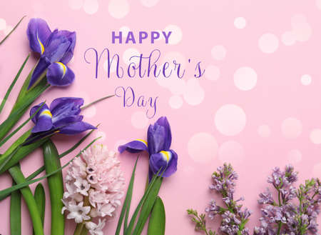 Flat lay composition with beautiful spring flowers and phrase HAPPY MOTHER'S DAY on light pink background