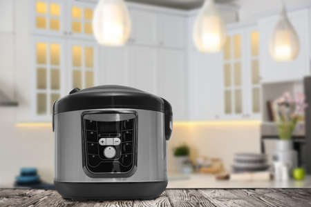 Modern electric multi cooker on wooden table in kitchen. Space for design