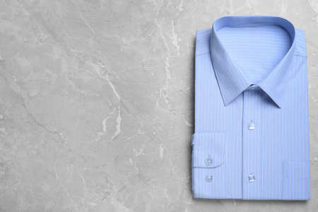 Stylish light blue shirt on grey marble table, top view with space for text. Dry-cleaning service