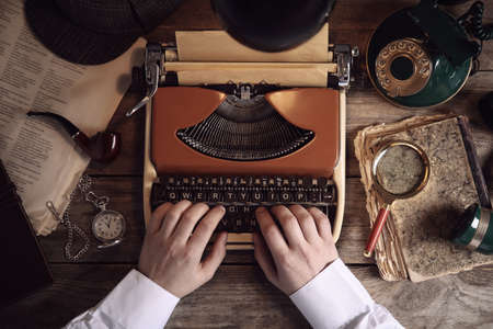 Detective working on vintage typewriter at wooden table, top view Stock Photo